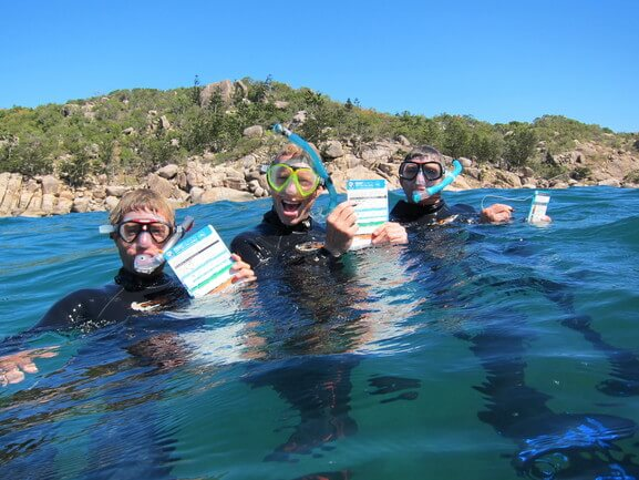 Three men snorkelling and holding checklists